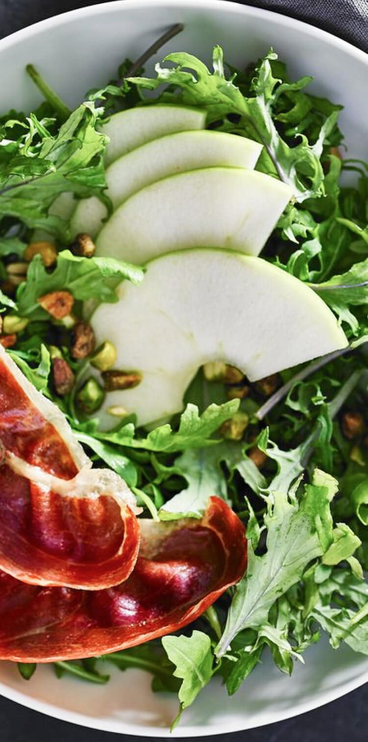 An arugula salad in a white bowl sprinkled with pistachios and thinly sliced green apples.