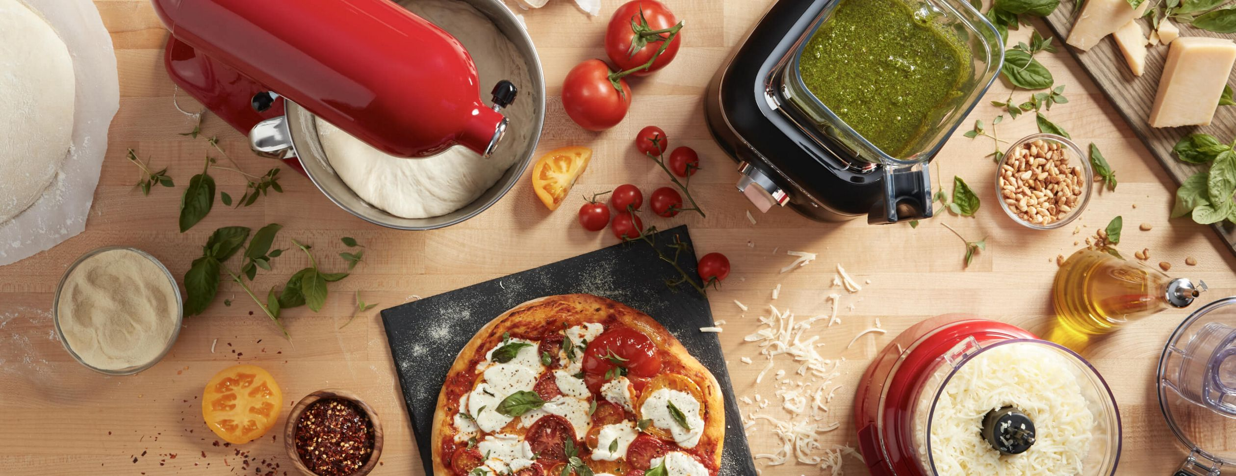 A table full of fresh ingredients with KitchenAid countertop appliances making pizza.