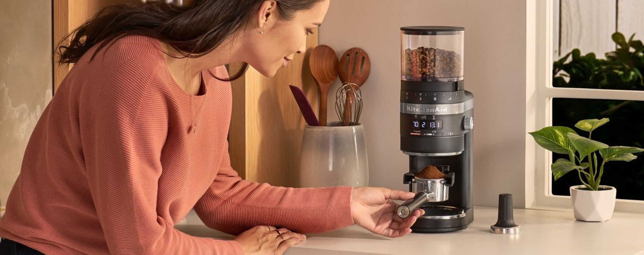 A person happily using a KitchenAid® Burr Coffee Grinder.