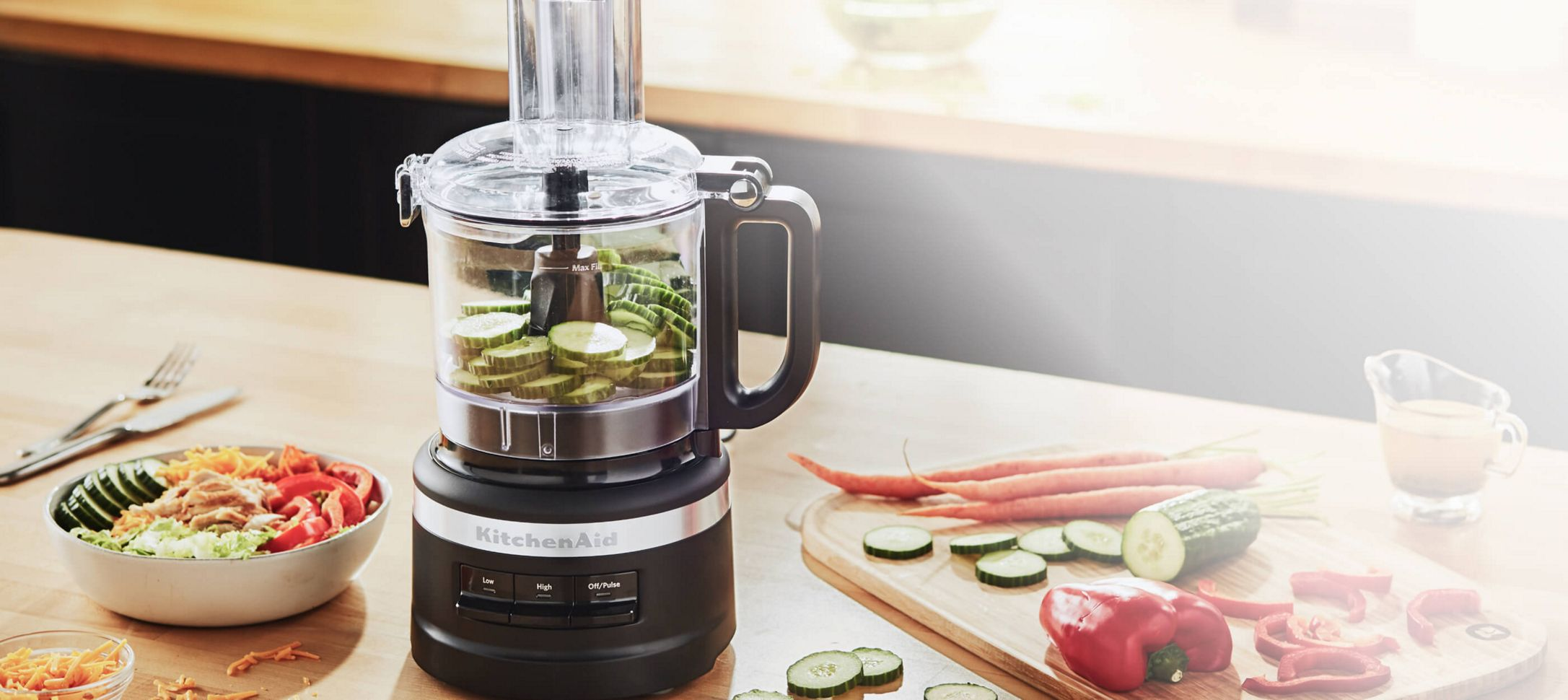A Black 7 Cup Food Processor filled with sliced cucumbers.
