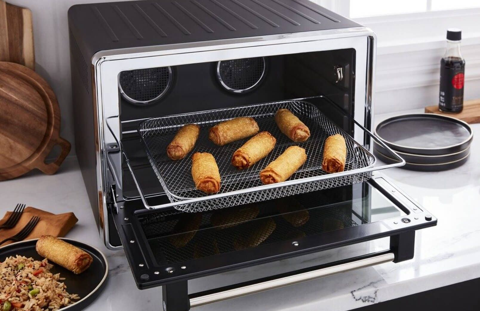 A KitchenAid® Dual Convection Countertop Oven with Air Fry frying egg rolls.