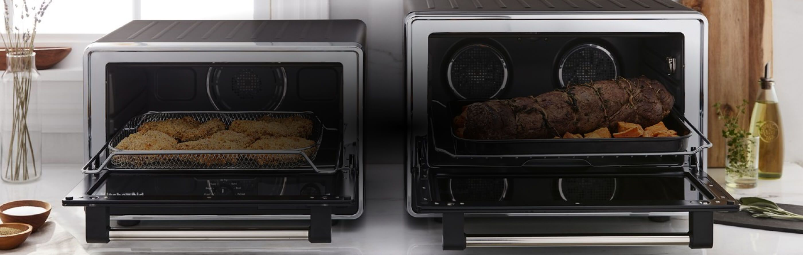 Two KitchenAid® Countertop Ovens resting on a kitchen counter.