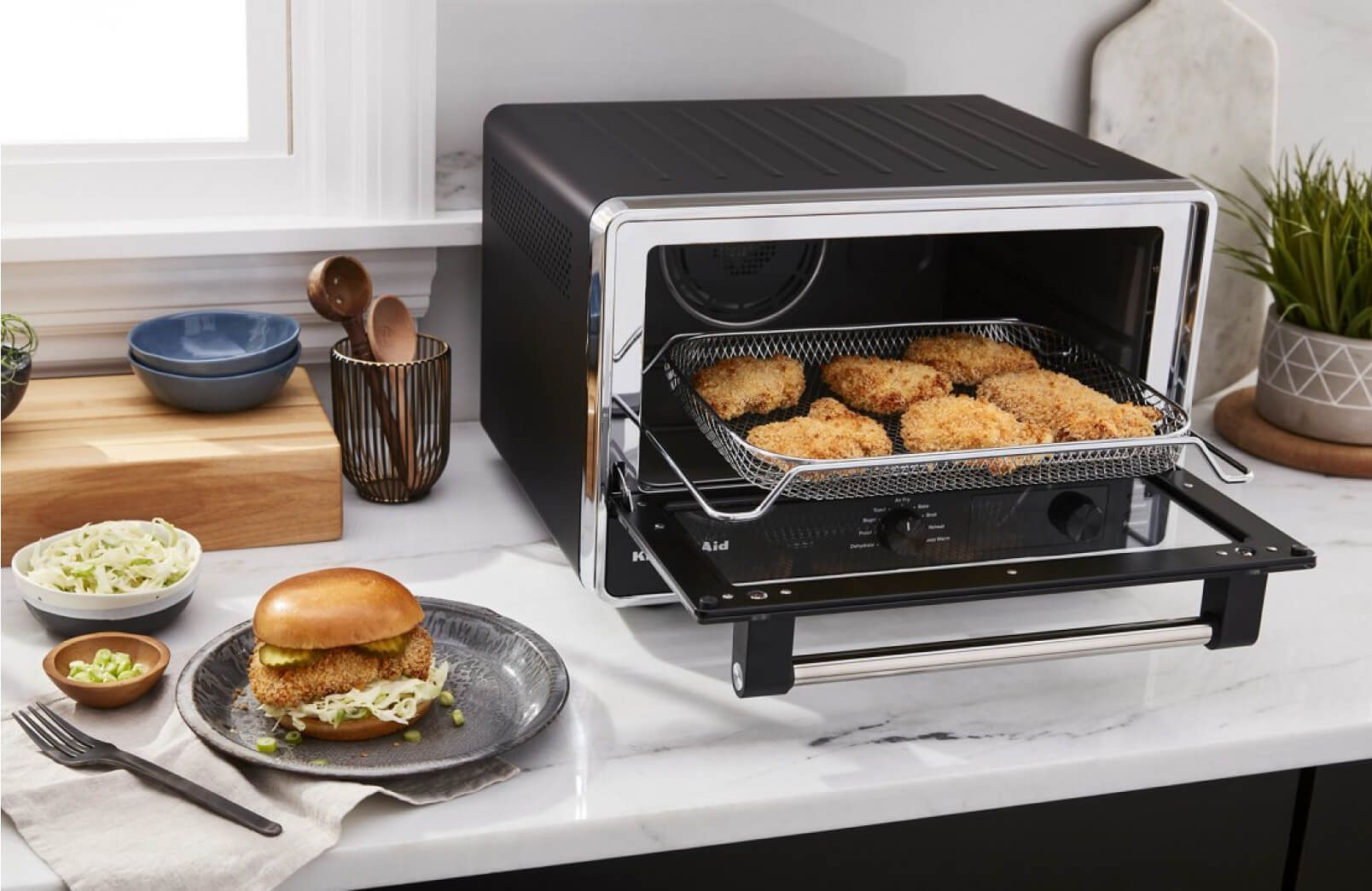 A KitchenAid® Digital Countertop Oven with Air Fry frying chicken.