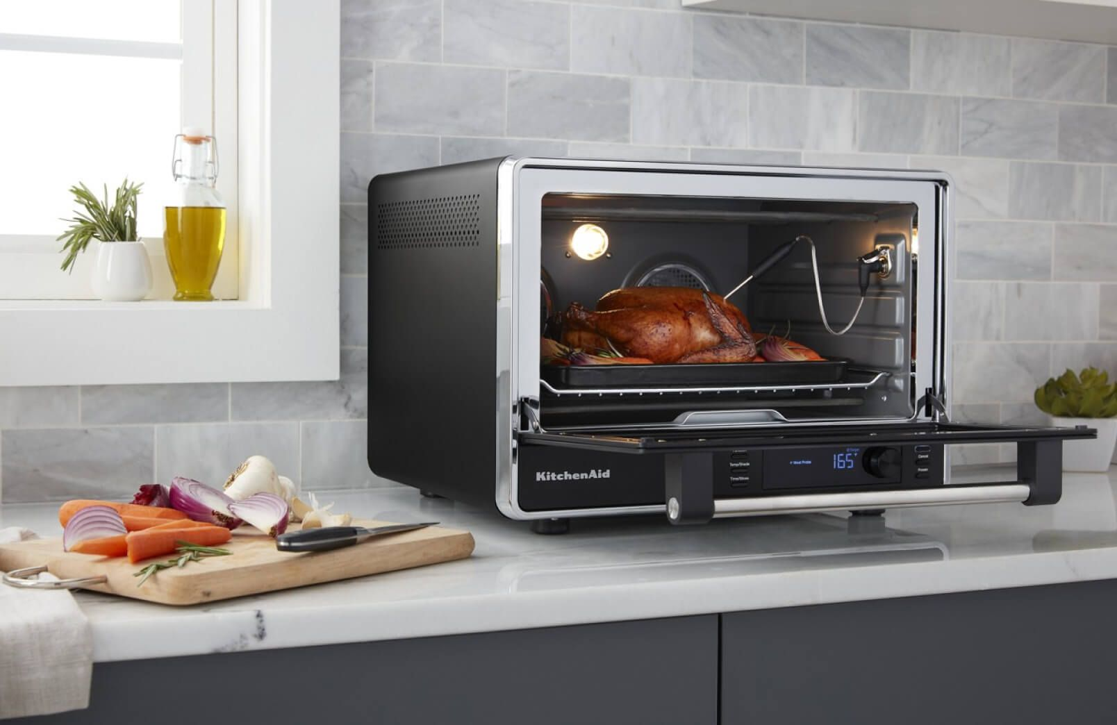 A KitchenAid® Dual Convection Countertop Oven roasting a whole chicken.