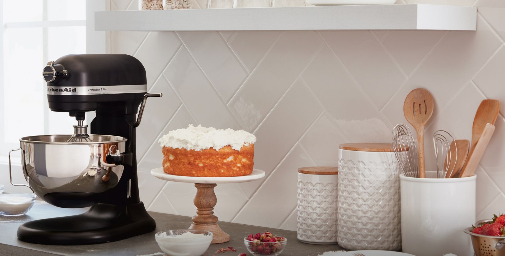 A KitchenAid® Stand Mixer on counter beside a cake