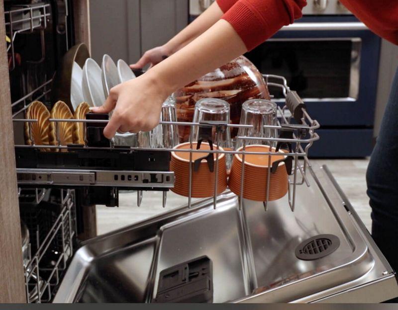 Woman adjusting loaded middle rack of dishwasher