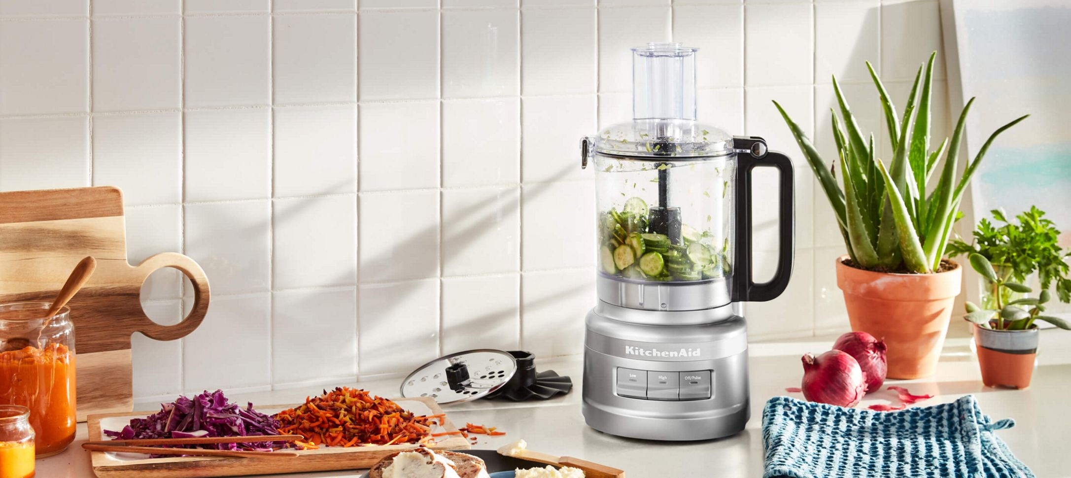 A Contour Silver 9 Cup Food Processor holding sliced cucumber.