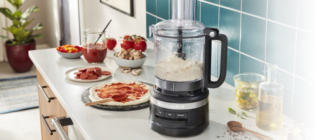 A Matte Black 9 Cup Food Processor filled with dough.