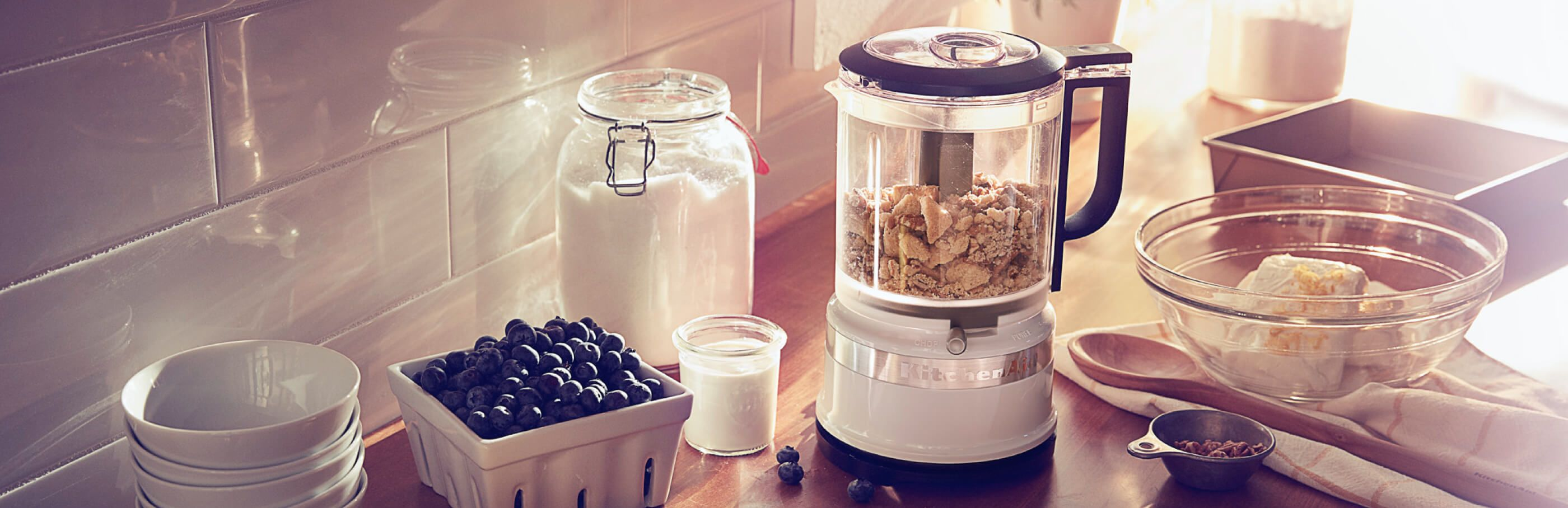 A White KitchenAid® food processor on a wooden countertop with blueberries and other ingredients.