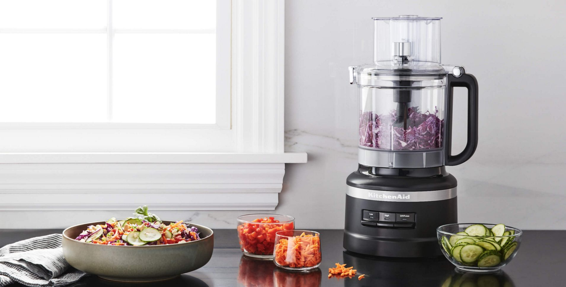 A Contour Silver KitchenAid® food chopper holding various ingredients and seasonings.
