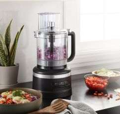 A Matte Black 13 Cup Food Processor holding red cabbage.