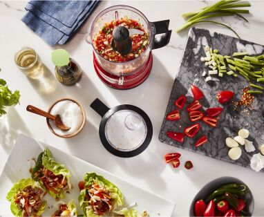 A Red KitchenAid® food chopper holding a red sweet pepper salsa for fresh lettuce wraps.