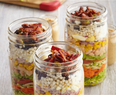 Three tall, glass mason jars filled with chopped ingredients for to-go salad.