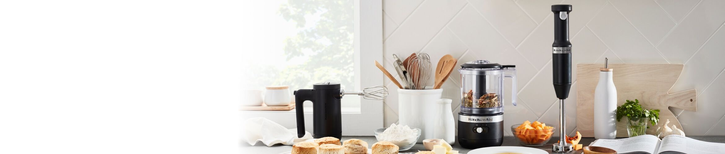 A sun-filled countertop featuring the Matte Black Cordless Chopper, Hand Mixer and Hand Blender.