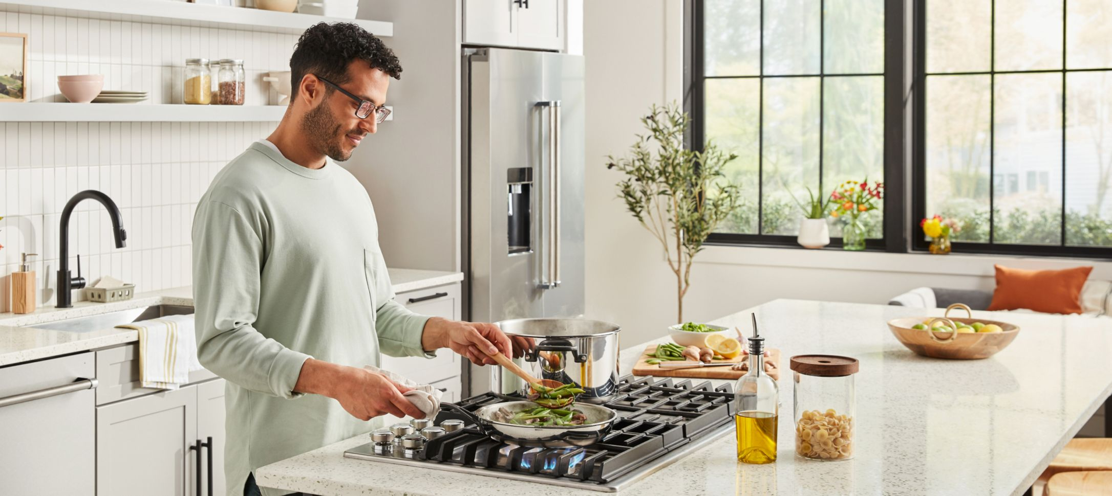 A person cooking over a cooktop in a bright, clean kitchen.