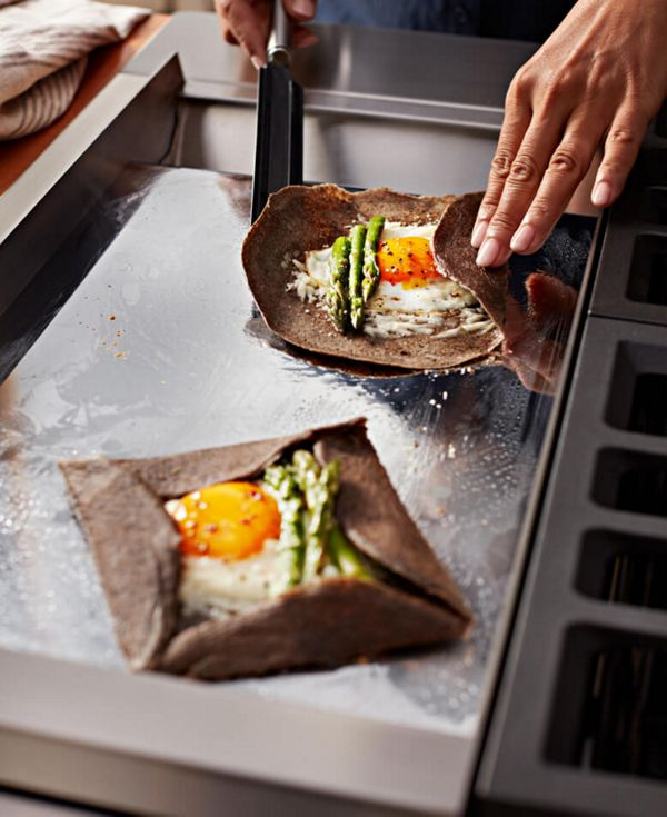 Sunny-side up eggs and asparagus being wrapped in a tortilla on the griddle.