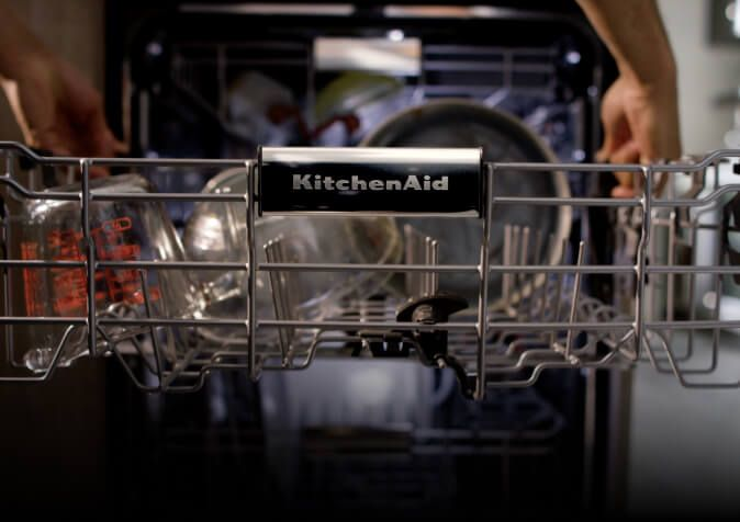 A close-up of the dishwasher's middle rack fully extended to be loaded up.