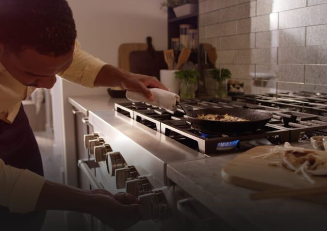 Man adjusting temperature while sautéing on a stainless steel range.