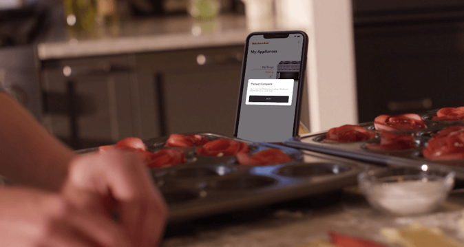 Person using Kitchenaid app while preparing pastries on counter.