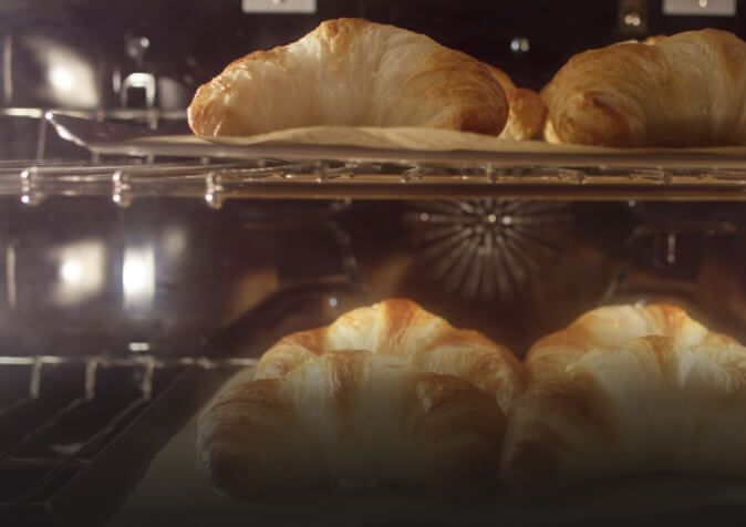 Close-up of croissants baking in convection oven.