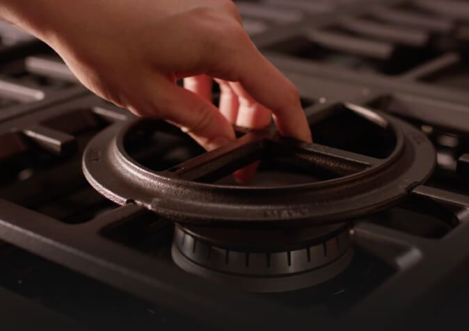 Close-up of hand placing convertible grate above burner.