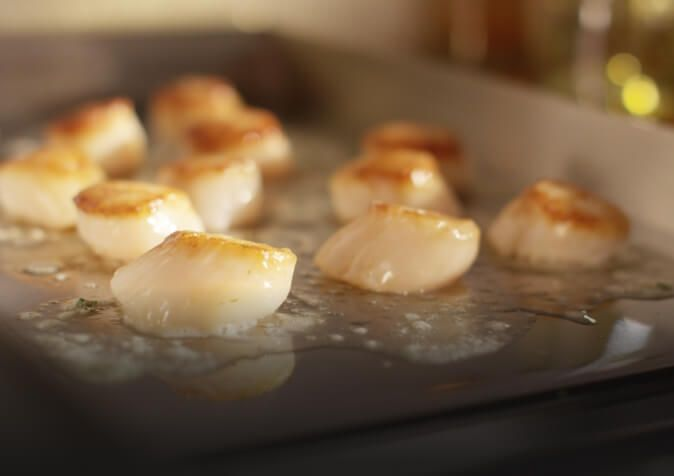 Close-up of scallops sizzling on electric burner.