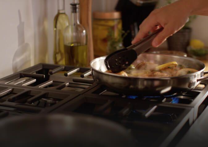 Person sautéing vegetables on rangetop burner.