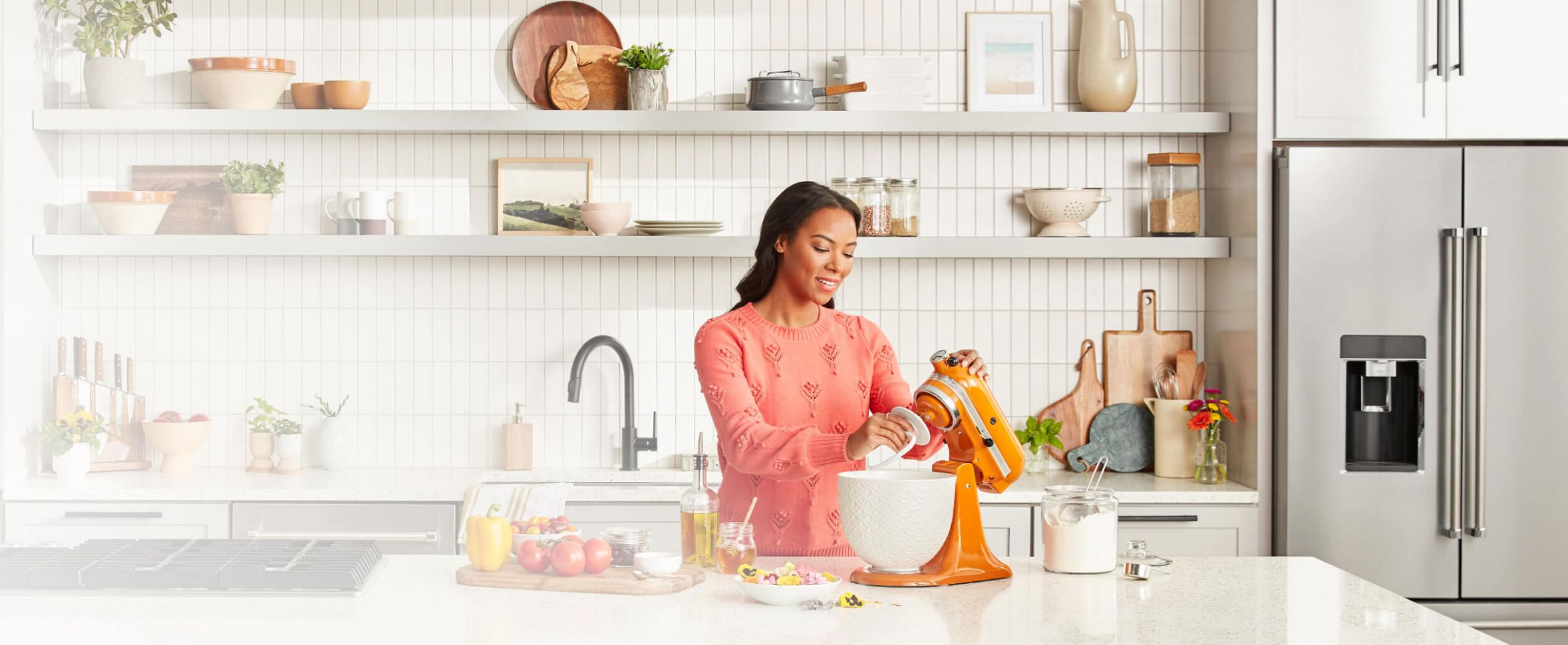 Woman in white kitchen lifting head of KitchenAid® Stand Mixer in Honey fitted with dough hook attachment.