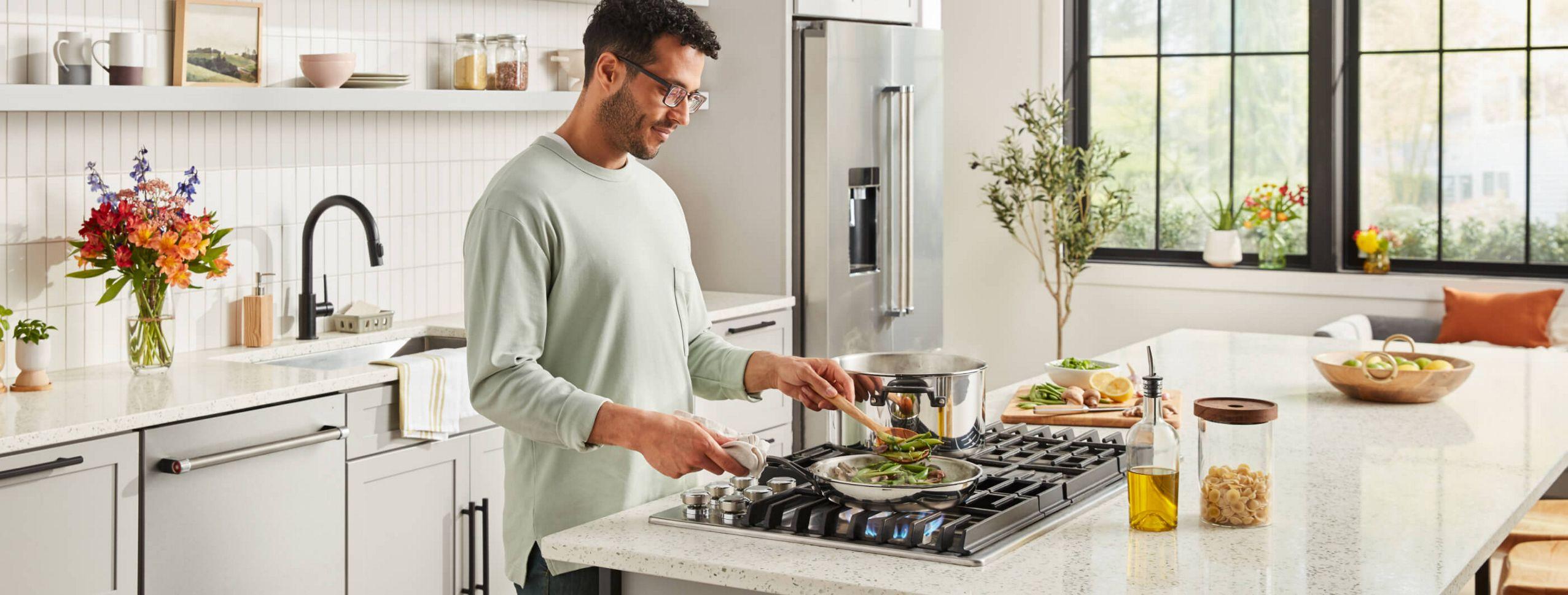 Man in grey shirt standing at KitchenAid® Cooktop sauteing green vegetables.