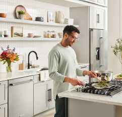 Man in grey shirt standing at KitchenAid® Cooktop sauteing green vegetables.