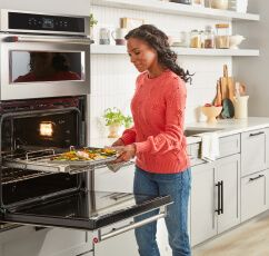 Woman in white kitchen placing sheet pan in KitchenAid® Combination Wall Oven.