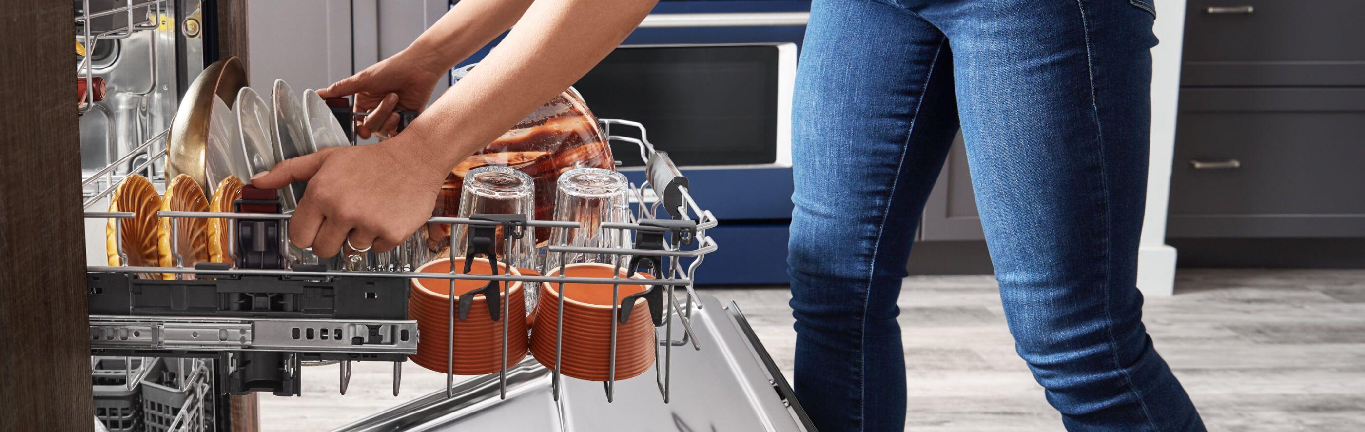 Woman adjusting upper rack in loaded dishwasher