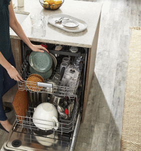 Woman loading small plates into KitchenAid® Dishwasher with Third Level Utensil Rack
