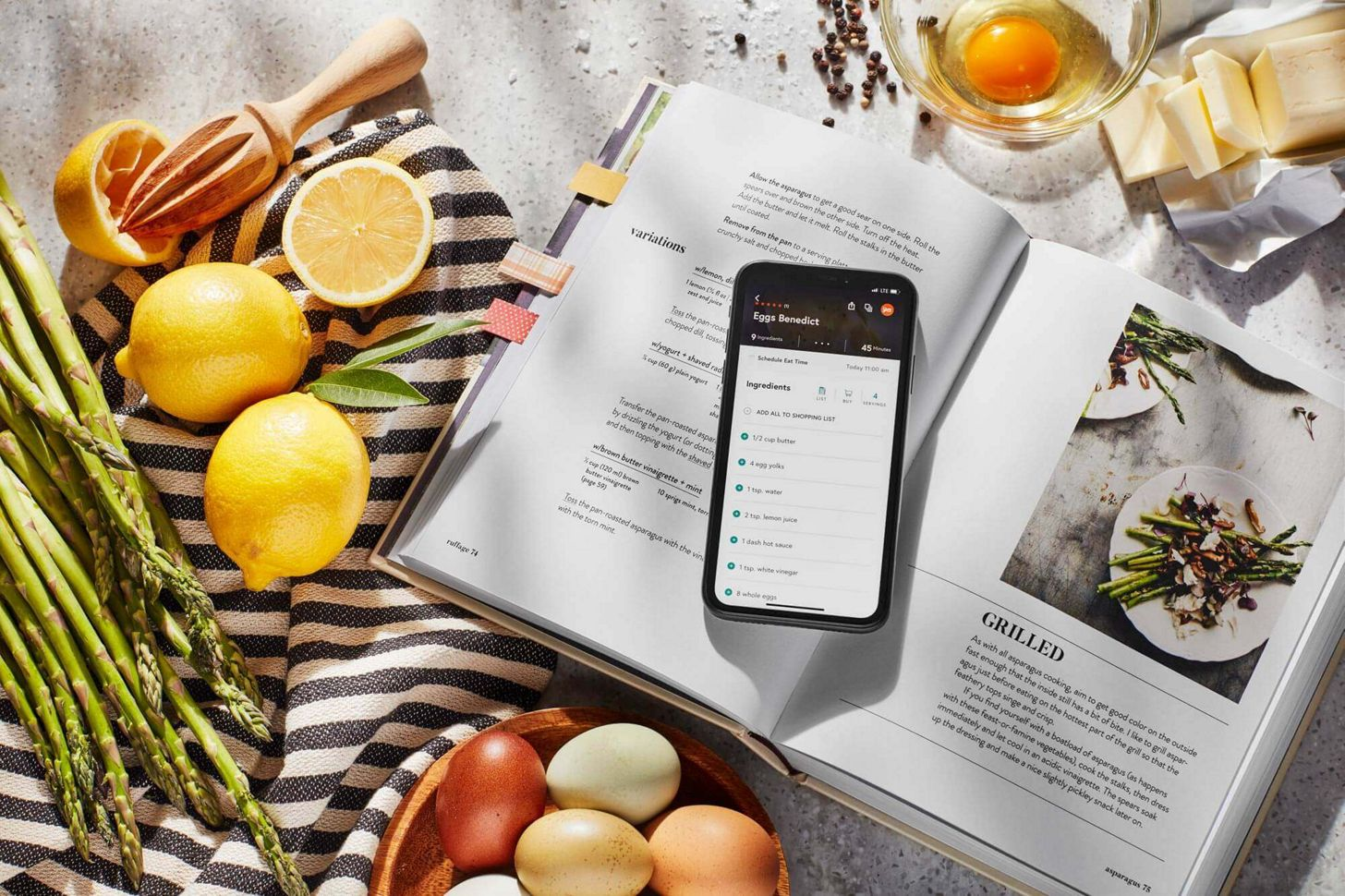A phone opened up to an eggs benedict recipe resting on an open book's grilled asparagus recipe.