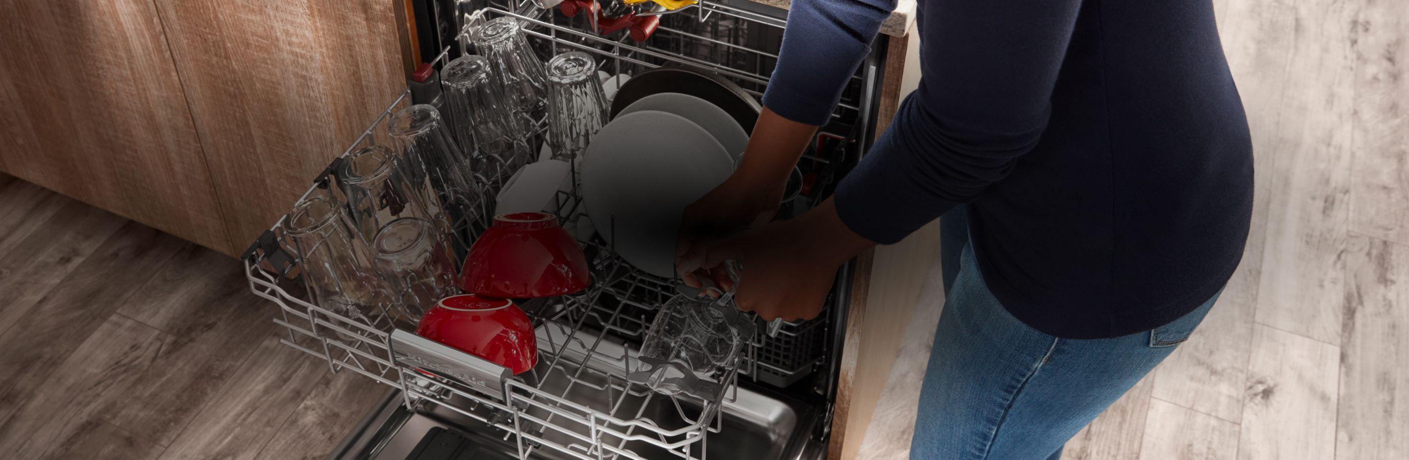 Loading a KitchenAid® dishwasher.