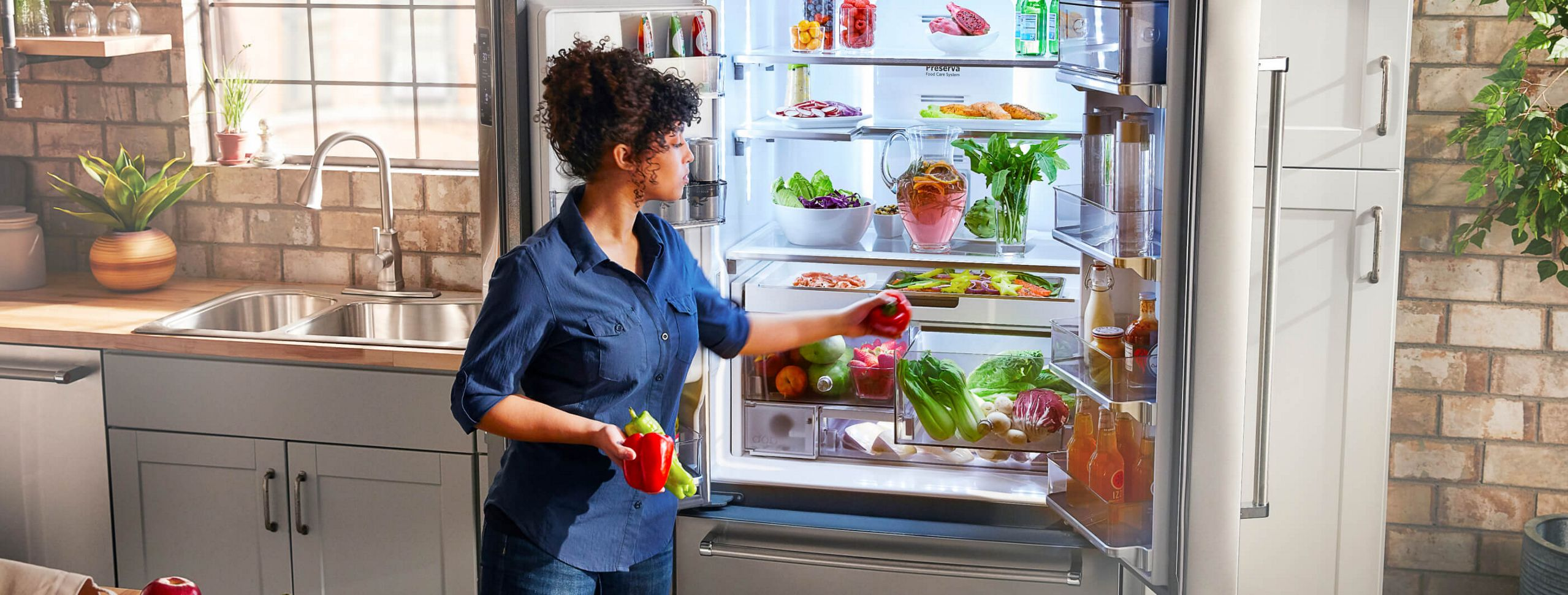 A person putting away fresh veggies in her refrigerator.