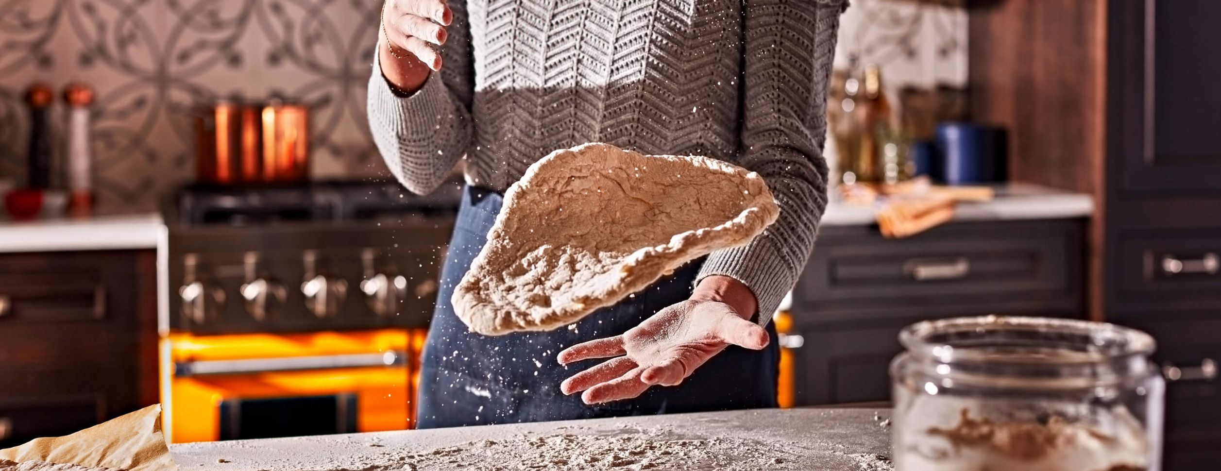 A skillful Maker in mid-throw of handmade pizza dough.