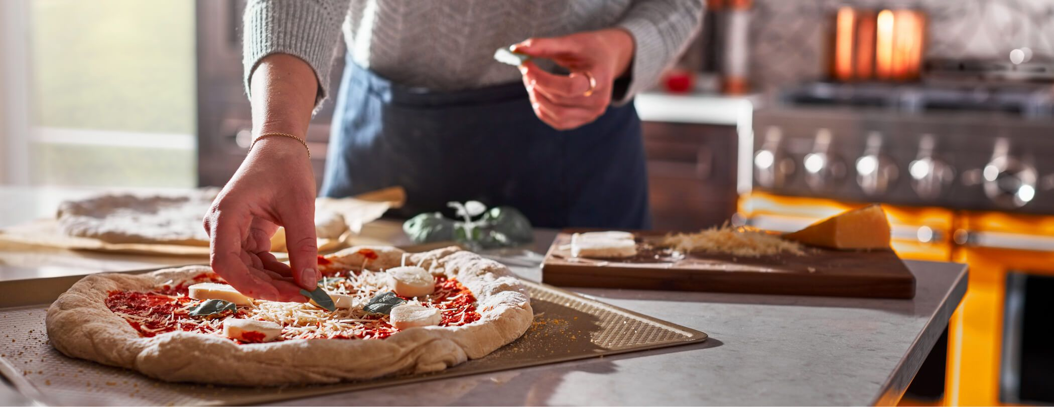 A person dressing pizza in the kitchen, featuring a Scorched Orange commercial-style range.