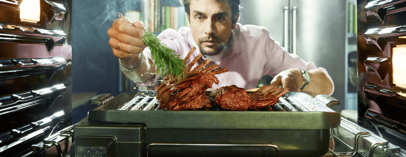 A view from inside an oven, as a man intently pulls out the grill attachment to add some finishing touches to a roast he's preparing.
