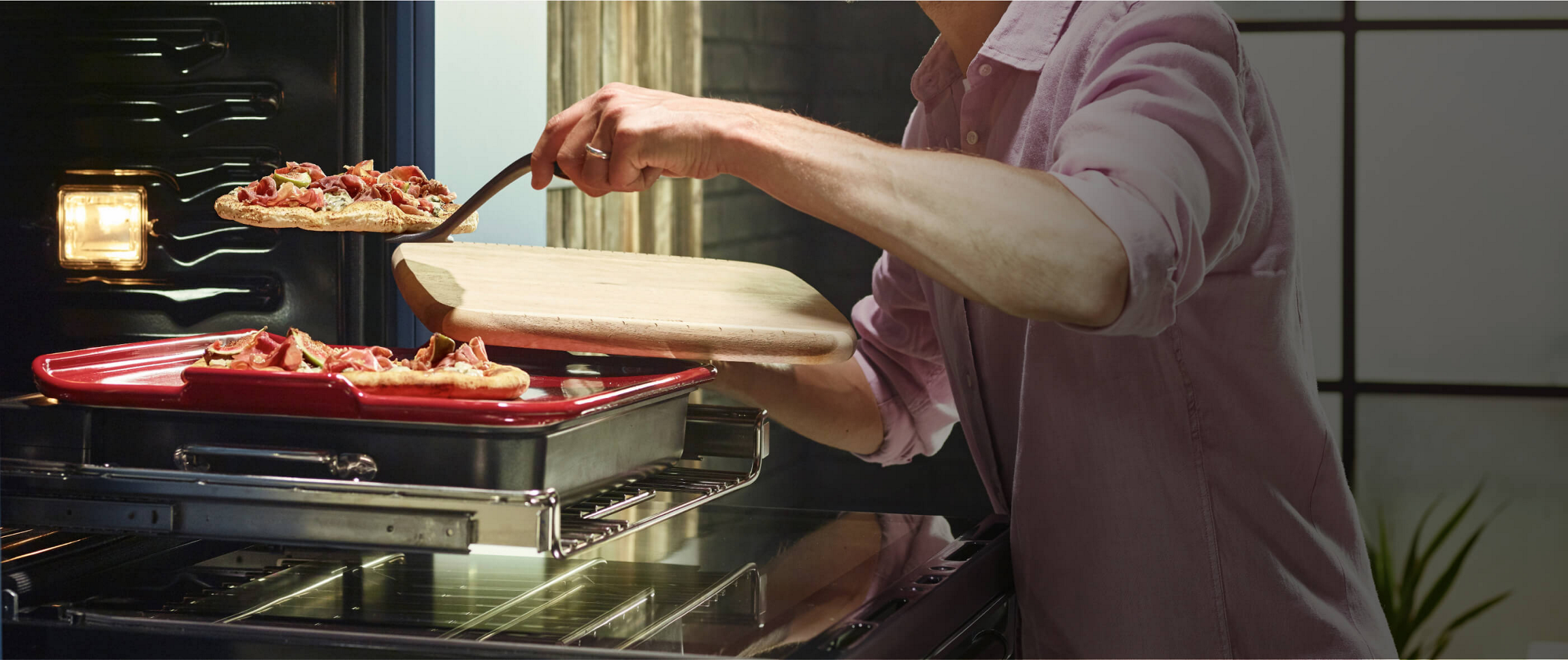 A Smart Oven Plus, open with the pizza stone attachment slid forward. A Maker transfers one of two gourmet pizza onto a cutting board for service.