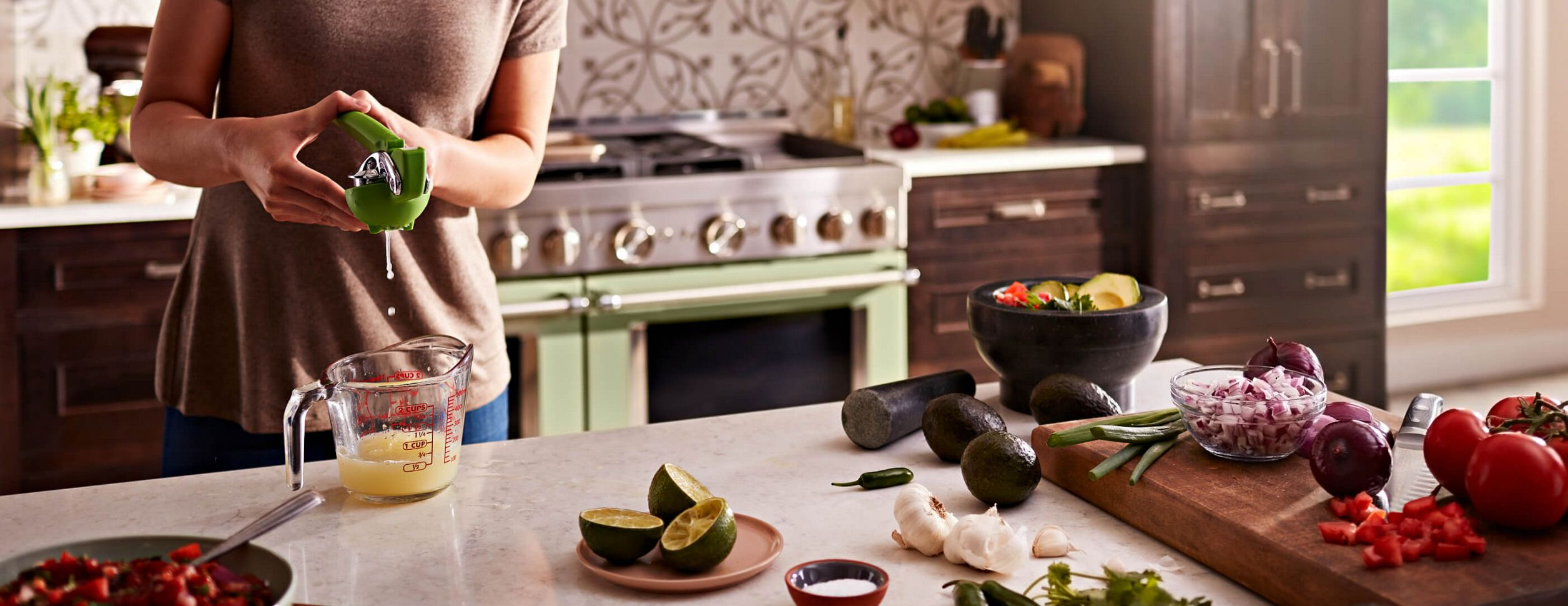 A young woman passionately working in her kitchen, featuring an Avocado Cream commercial-style range.