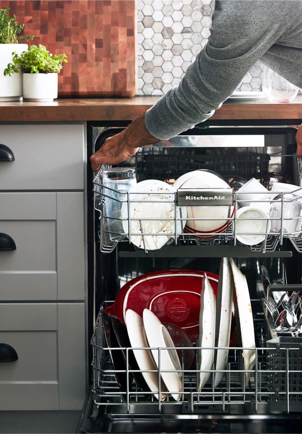 On the left, an open dishwasher viewed from above — packed with the aftermath of good cooking and a great meal.