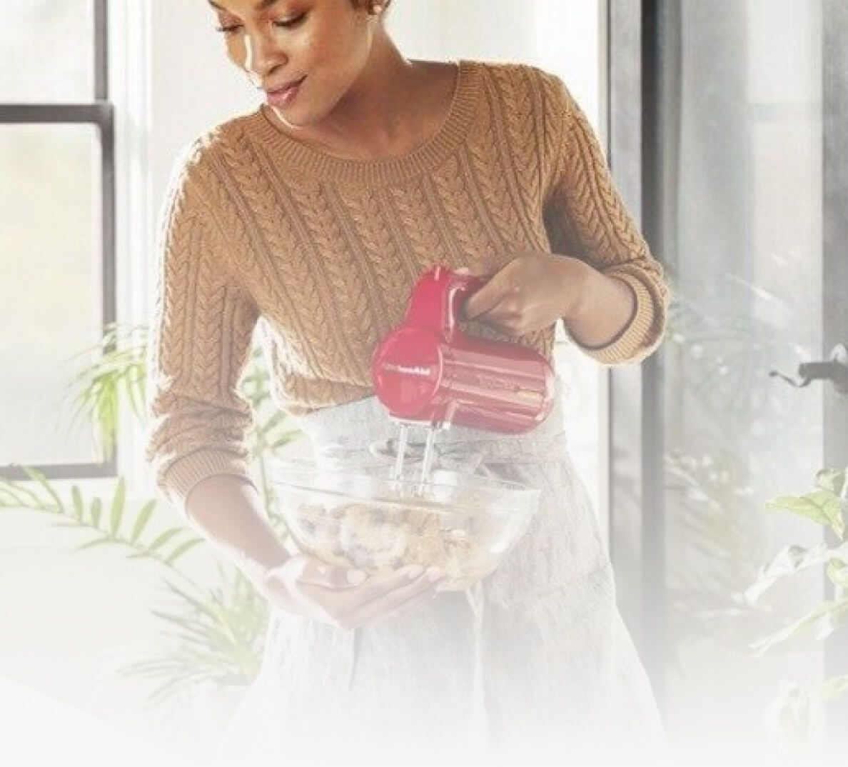 A person using a KitchenAid® hand mixer.