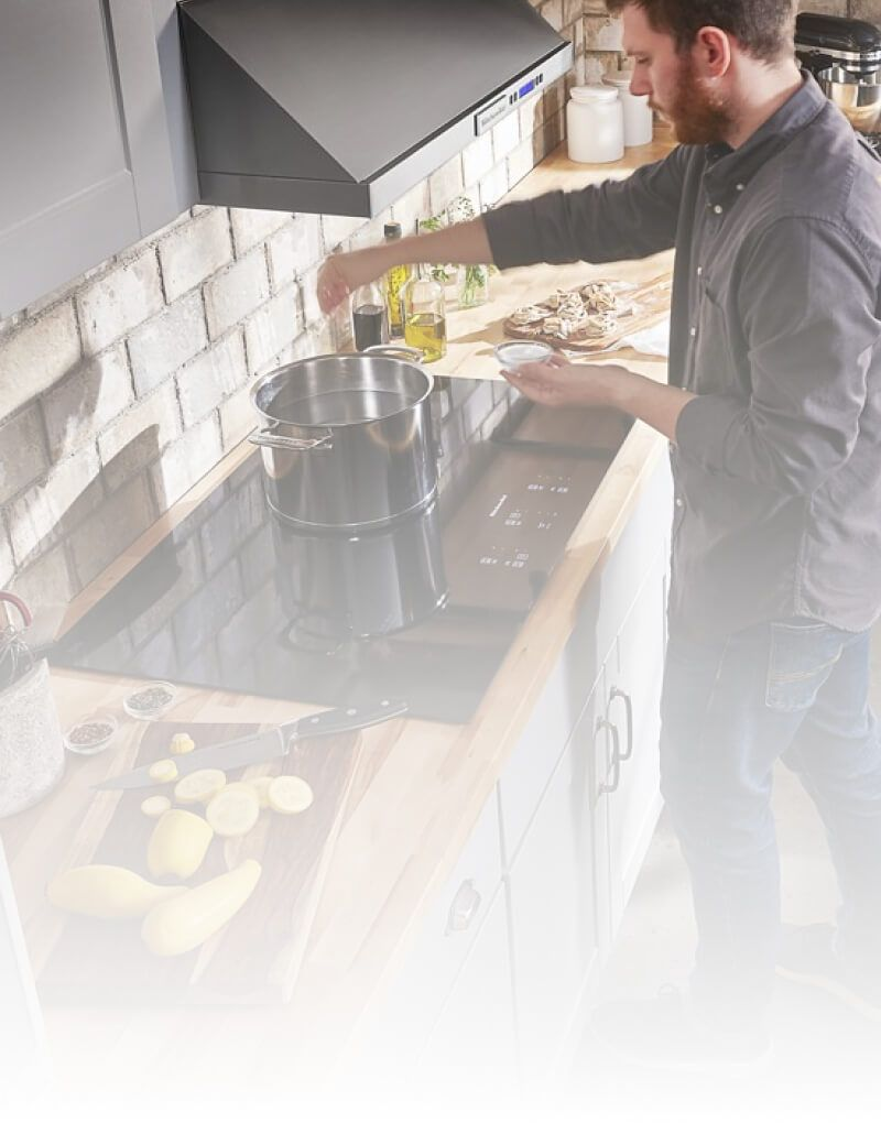 A person cooking on a KitchenAid® Cooktop.