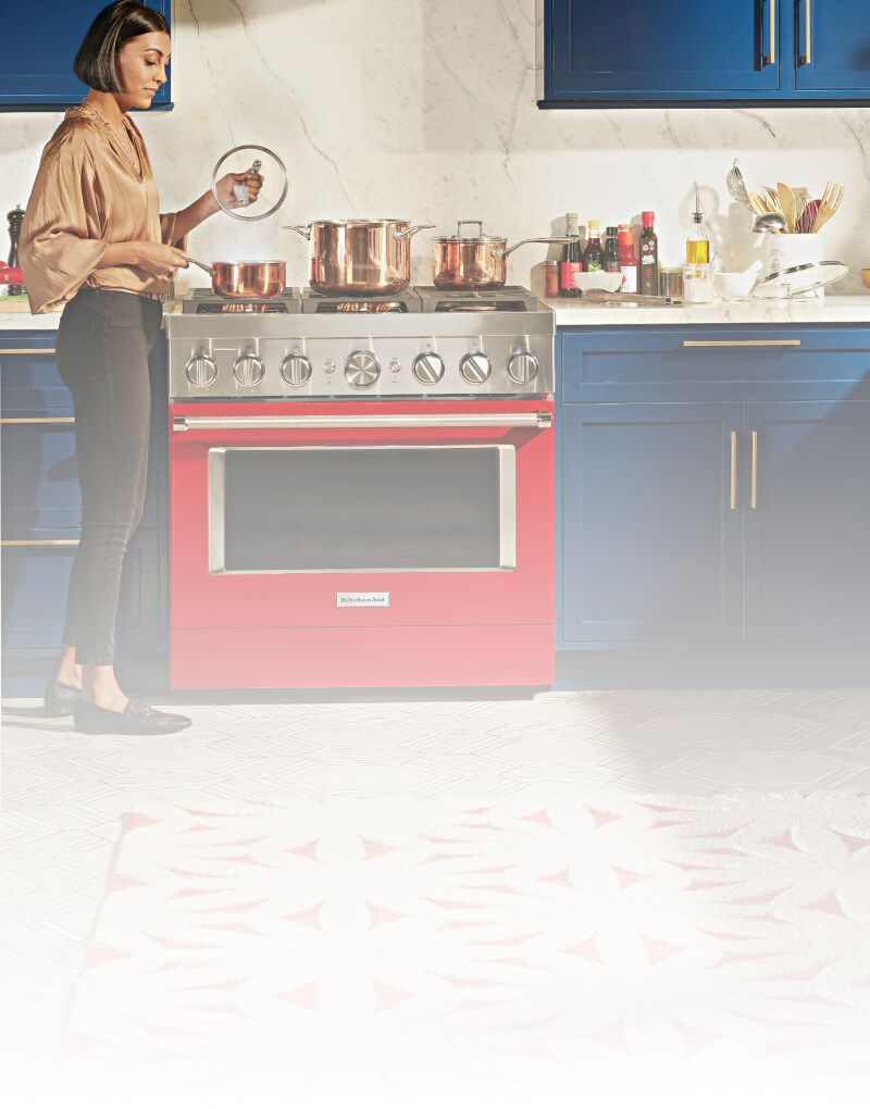 A person cooking with a KitchenAid® Commercial-Style Range.