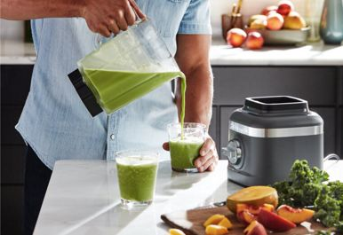 Man pouring a green smoothie from a KitchenAid® refurbished blender jar.
