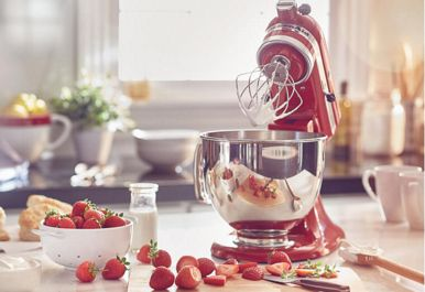 Refurbished KitchenAid® mixer with wire whip and stainless steel bowl making whipped cream.