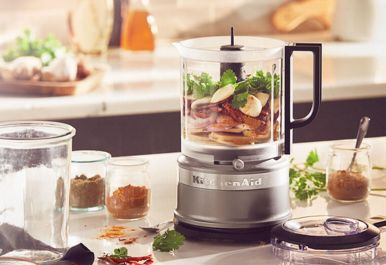 Silver refurbished food processor filled with ingredients.