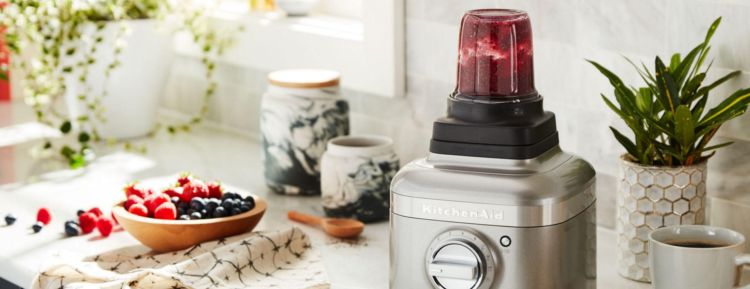 A KitchenAid food processor, loaded with a variety of colorful vegetables. All around it are the signs of preparation, with cut and uncut ingredients in various states of preparation.