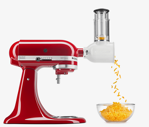 Red stand mixer with shredder attachment shredding cheddar cheese.